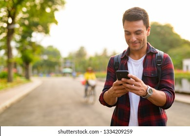 Happy young handsome Hispanic hipster man using phone at the park