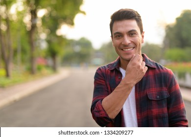 Happy young handsome Hispanic hipster man smiling at the park