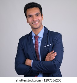Happy young handsome Indian businessman smiling with arms crossed