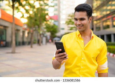 Happy young handsome Indian man using phone in the city street