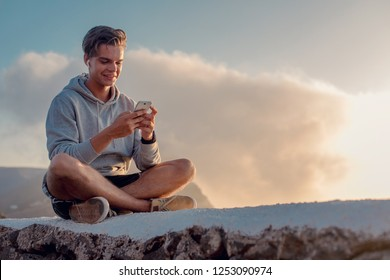 Happy young handsome man messaging on his smartphone, while sitting on a mountain hill against beautiful cloud in sunset sky.