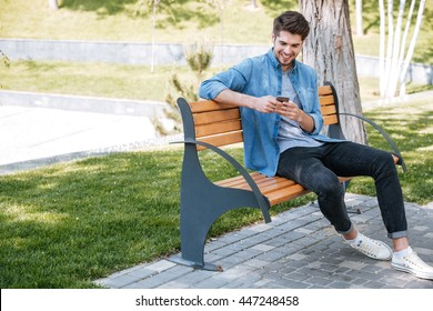 Happy young handsome man sitting on the bench outdoors and using smartphone