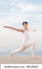 Happy young healthy woman doing yoga exercise outdoor at sea