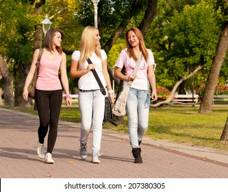 happy young high school students or college girls smiling walking to school through the park/happy young high school students