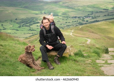 Happy young hiker with his little daughter in backpack child carrier and a dog, resting in the mountains.