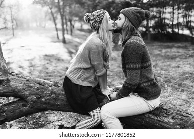 Happy young hipster couple in love kissing and hugging in sunny park. Cold season. Romantic mood. Wearing knitted trendy sweater and bright hat. Black and white.