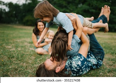 Happy young hipster family having fun, bowl,  rising up, piggyback ride their children in park on summer sunset