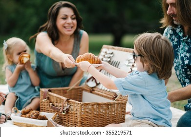 Happy young hipster family having fun, bowl, rising up, piggyback ride their children and relax for a picnic with basket full of milk and croissants in park on summer sunset