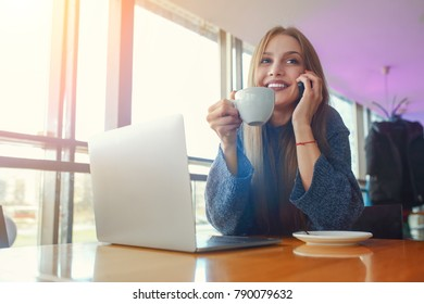 Happy young hipster woman with cup of cofe talking on the phone in at cafe. Laptop on the table.