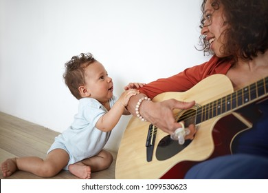 Happy young Hispanic female musician sitting on floor, playing guitar to her adorable cute baby son who is singing along with her, Music, art, talent, creativity, infancy, education and childcare