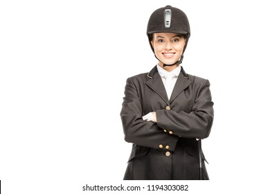 happy young horsewoman in uniform and helmet looking at camera with crossed arms isolated on white