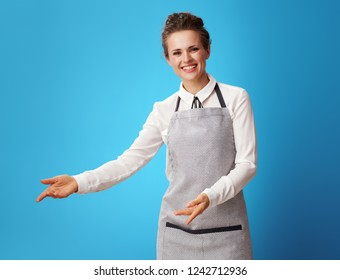 happy young housemaid in apron welcoming isolated on blue background. Housemaid invites customers to evaluate the quality of the cleaning service