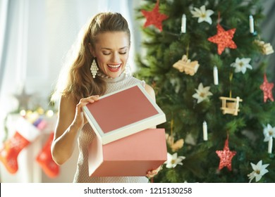 happy young housewife near Christmas tree opening Christmas present box