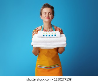 happy young housewife in orange apron enjoying fresh white linen on blue background. How to keep towels soft and luxurious? Choose a high-quality, effective washing powder