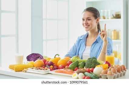 happy young housewife sitting in the kitchen preparing food from a pile of diverse fresh organic fruits and vegetables, selective focus