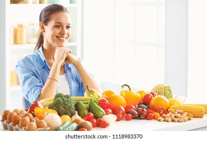 happy young housewife sitting in the kitchen preparing food from a pile of diverse fresh organic fruits and vegetables