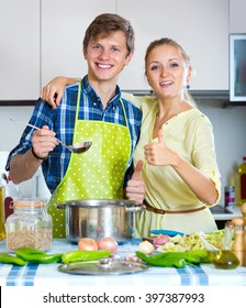 Happy young husband helping wife to prepare healthy dinner