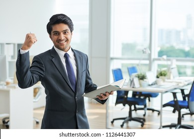 Happy young Indian businessman celebrating success