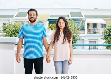 Happy young Indian couple in casual clothes holding hands and looking at camera when standing on balcony