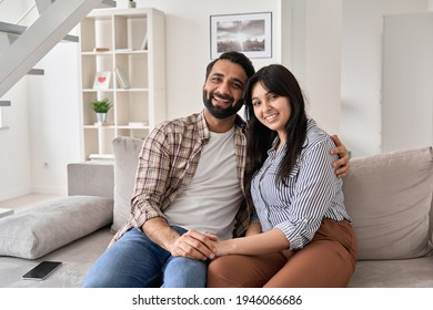Happy young indian couple real estate buyers hugging sitting on couch at home looking at camera. Smiling husband and wife new homeowners embracing, enjoying own apartment purchase, portrait.