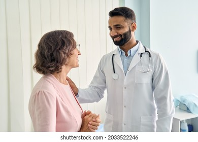 Happy young Indian doctor therapist in white coat has appointment consulting supporting putting hand on shoulder of older senior female patient in modern clinic hospital. Medical healthcare concept.