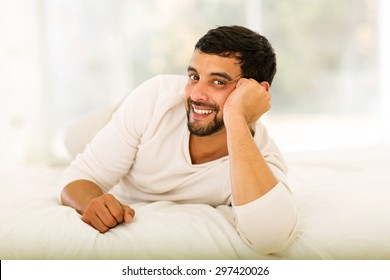 happy young indian man lying on bed at home