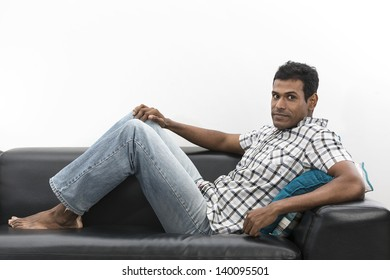 Happy young Indian man relaxing on sofa at home