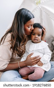 Happy young Indian mother playing kissing mixed race black baby girl daughter. Family mixed race people mom and kid together hugging embracing at home. Ethnic diversity family.