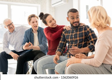 Happy young intercultural woman keeping her hands on shoulders of her husband or boyfriend consulting with psychologist