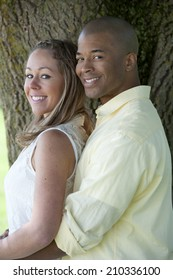 A happy and young Interracial couple posing on a sunny day under a tree