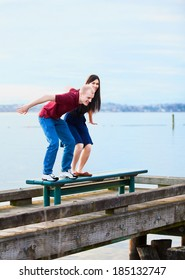 Happy young interracial couple  preparing to jump off  dock over lake, playful