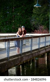 Happy young interracial couple standing on bridge over water