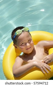 Happy young kid relaxing in a sparkling pool