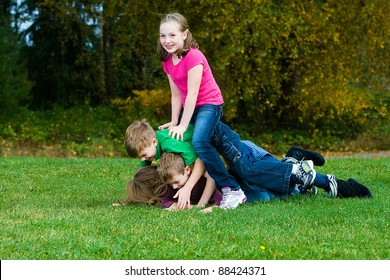 Happy young kids playing outside piled on top of each other on a field of grass.
