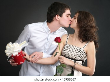Happy young kissing couple with gift and red rose