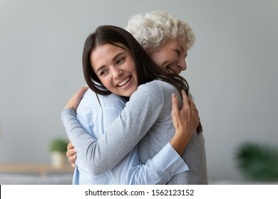 Happy young lady adult daughter granddaughter visiting embracing hugging old senior retired grandmother cuddling bonding, two age generations women expressing love and care at reunion meeting at home