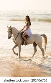 happy young lady enjoying horse ride on beach