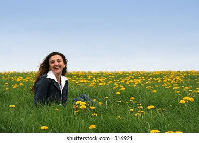 A happy young lady in a flowering spring field with blue jacket