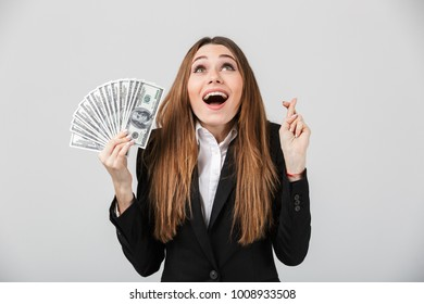 Happy young lady looking camera with opened mouth and holding prey gesture while showing cash dollars isolated