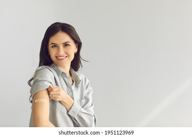 Happy young lady on gray empty blank text copyspace studio background looking at camera, smiling and showing arm after vaccine injection. Coronavirus, Covid-19, flu vaccination and immunization