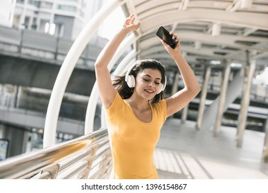 Happy young Latino woman listening to music from headphones and dancing with hands up in city covered walkway