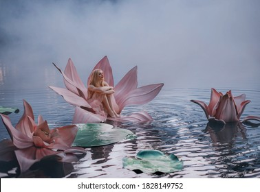 Happy young little blonde woman sits in huge pink flower lotus on water. Fantasy artistic photo. Beautiful girl in a fairy tale lake. Girl Thumbelina. Image Goddess of nature in blue mystic river fog