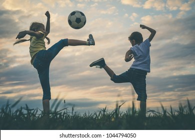Happy young little boy and girl playing in the field  with soccer ball.  Kids having fun outdoors. Concept of sport.