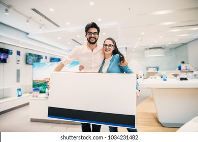 Happy young lovely modern couple with bought big tv in the electronic store.