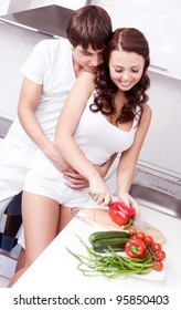 happy young loving couple cooking together in the kitchen at home