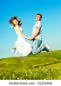 happy young loving couple jumping outdoor in summertime