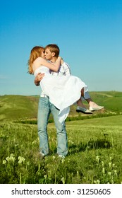 happy young loving couple kissing outdoor in summertime