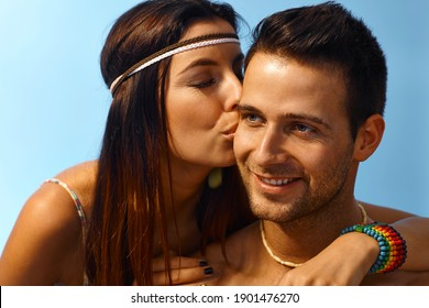 Happy young loving couple outdoors at summertime, woman kissing man on the face.