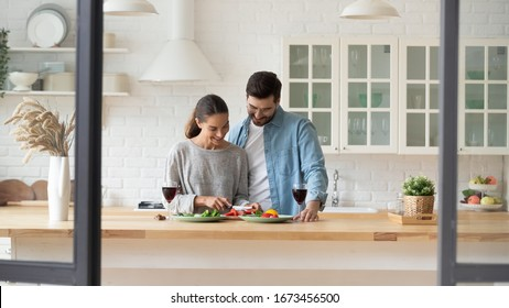 Happy young loving couple preparing dinner in kitchen at home together, celebrating anniversary, enjoying romantic date, drinking red wine, smiling beautiful wife cutting vegetables for salad