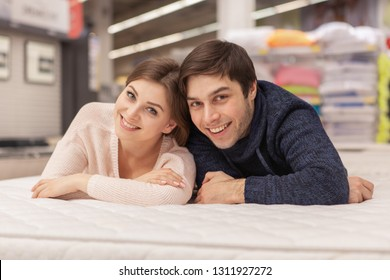 Happy young loving couple smiling to the camera joyfully, lying on orthopedic mattress at home furnishings store. Beautiful woman and her husband shopping for bedding and furniture